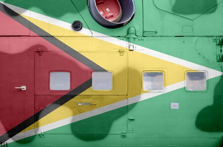Guyana flag depicted on side part of military armored helicopter close up. Army forces aircraft conceptual background Stock fotó