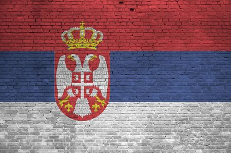 Serbia flag depicted in paint colors on old brick wall close up. Textured banner on big brick wall masonry background