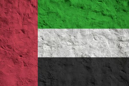 United Arab Emirates flag depicted in bright paint colors on old relief plastering wall close up. Textured banner on rough background