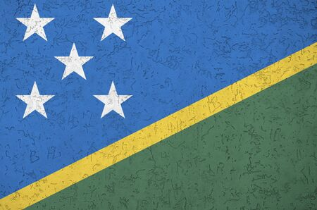 Solomon Islands flag depicted in bright paint colors on old relief plastering wall close up. Textured banner on rough background