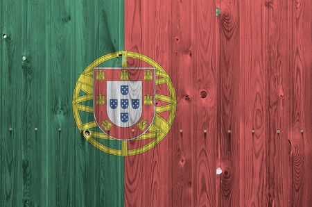 Portugal flag depicted in bright paint colors on old wooden wall close up. Textured banner on rough background