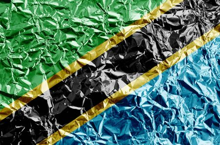 Tanzania flag depicted in paint colors on shiny crumpled aluminium foil close up. Textured banner on rough background Stock fotó