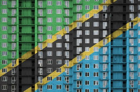 Tanzania flag depicted in paint colors on multi-storey residental building under construction. Textured banner on big brick wall background Stock fotó