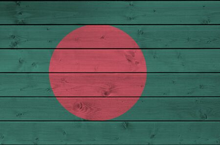 Bangladesh flag depicted in bright paint colors on old wooden wall close up. Textured banner on rough background