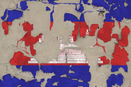 Cambodia flag depicted in paint colors on old obsolete messy concrete wall close up. Textured banner on rough background
