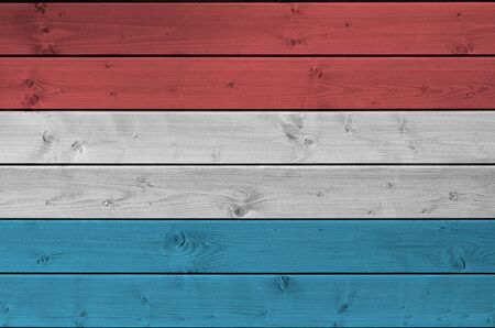 Luxembourg flag depicted in bright paint colors on old wooden wall close up. Textured banner on rough background