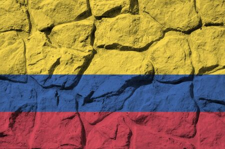 Colombia flag depicted in paint colors on old stone wall close up. Textured banner on rock wall background Stockfoto