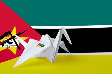 Mozambique flag depicted on paper origami crane wing. Oriental handmade arts concept Stock fotó
