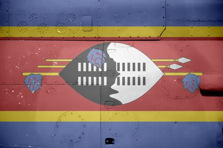 Swaziland flag depicted on side part of military armored helicopter close up. Army forces aircraft conceptual background