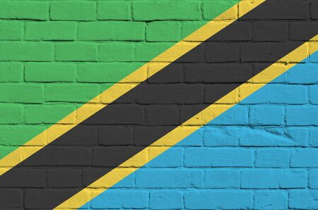 Tanzania flag depicted in paint colors on old brick wall close up. Textured banner on big brick wall masonry background