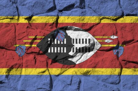Swaziland flag depicted in paint colors on old stone wall close up. Textured banner on rock wall background