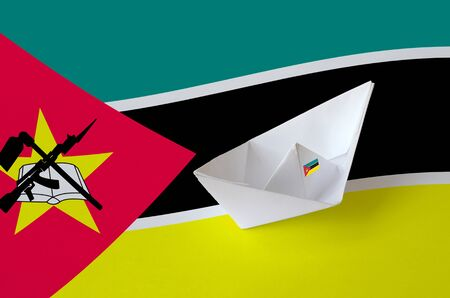 Mozambique flag depicted on paper origami ship closeup. Oriental handmade arts concept Stock fotó
