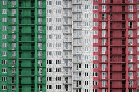 Italy flag depicted in paint colors on multi-storey residental building under construction. Textured banner on big brick wall background Reklamní fotografie