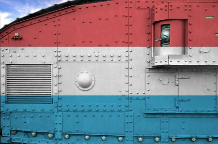 Luxembourg flag depicted on side part of military armored tank close up. Army forces conceptual background Imagens