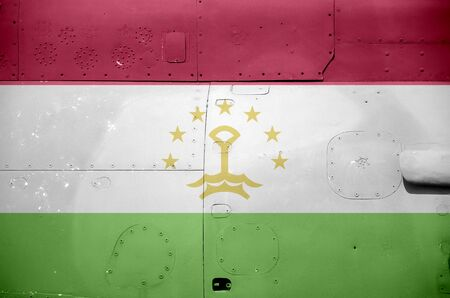 Tajikistan flag depicted on side part of military armored helicopter close up. Army forces aircraft conceptual background