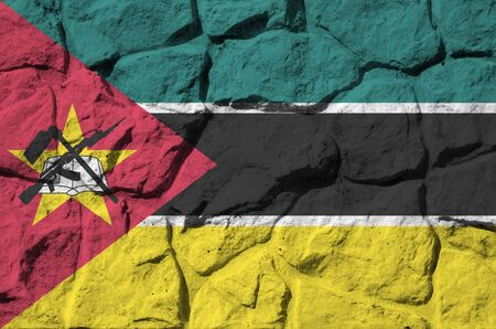 Mozambique flag depicted in paint colors on old stone wall close up. Textured banner on rock wall background