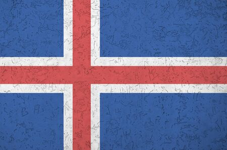 Iceland flag depicted in bright paint colors on old relief plastering wall close up. Textured banner on rough background Banco de Imagens