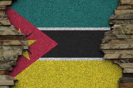 Mozambique flag depicted in paint colors on old stone wall close up. Textured banner on rock wall background Stock fotó