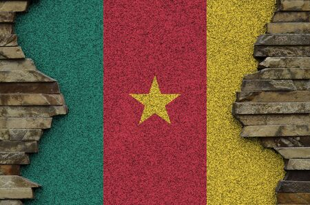 Cameroon flag depicted in paint colors on old stone wall close up. Textured banner on rock wall background