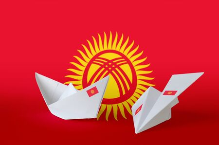 Kyrgyzstan flag depicted on paper origami airplane and boat. Oriental handmade arts concept