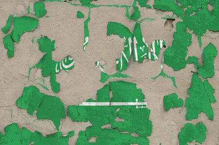 Saudi Arabia flag depicted in paint colors on old obsolete messy concrete wall close up. Textured banner on rough background