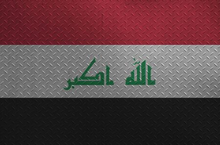 Iraq flag depicted in paint colors on old brushed metal plate or wall close up. Textured banner on rough background