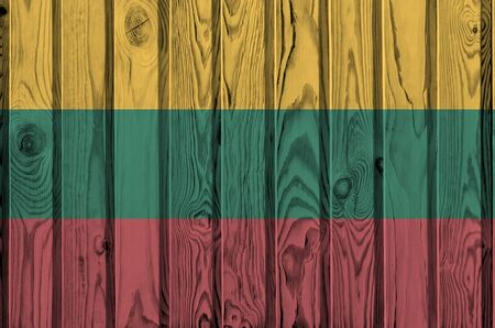 Lithuania flag depicted in bright paint colors on old wooden wall close up. Textured banner on rough background