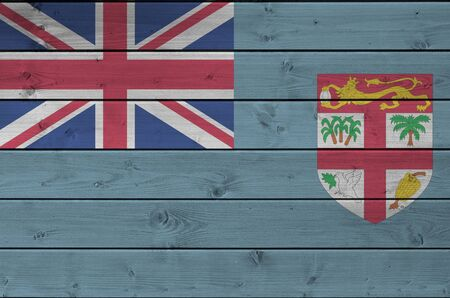 Fiji flag depicted in bright paint colors on old wooden wall close up. Textured banner on rough background Stock fotó