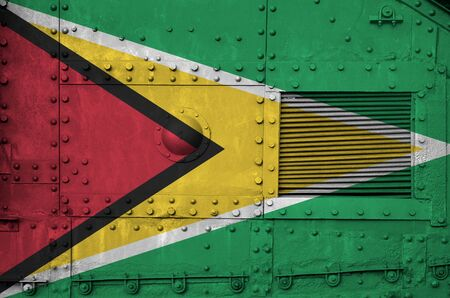 Guyana flag depicted on side part of military armored tank close up. Army forces conceptual background