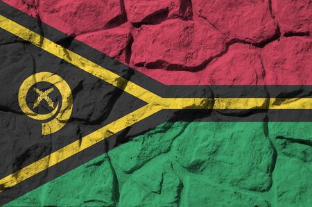 Vanuatu flag depicted in paint colors on old stone wall close up. Textured banner on rock wall background