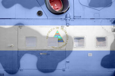 Nicaragua flag depicted on side part of military armored helicopter close up. Army forces aircraft conceptual background