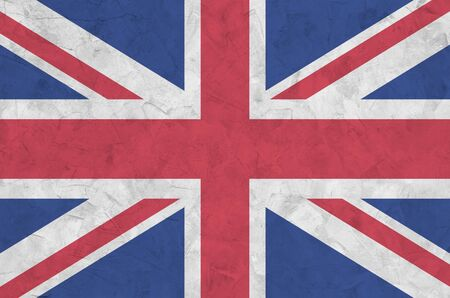 Great britain flag depicted in bright paint colors on old relief plastering wall close up. Textured banner on rough background