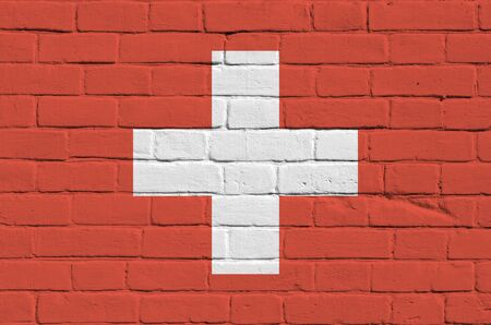 Switzerland flag depicted in paint colors on old brick wall close up. Textured banner on big brick wall masonry background