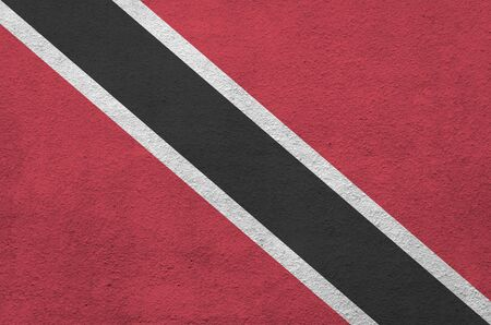 Trinidad and Tobago flag depicted in bright paint colors on old relief plastering wall close up. Textured banner on rough background