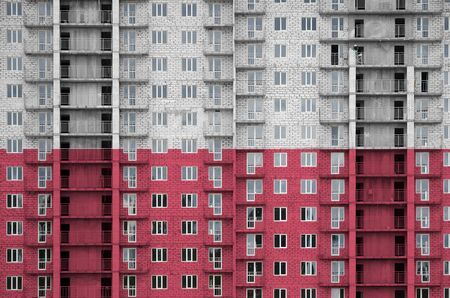 Poland flag depicted in paint colors on multi-storey residental building under construction. Textured banner on big brick wall background