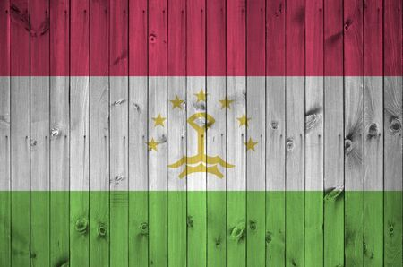 Tajikistan flag depicted in bright paint colors on old wooden wall close up. Textured banner on rough background