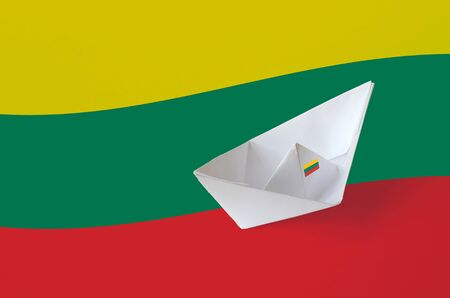 Lithuania flag depicted on paper origami ship closeup. Oriental handmade arts concept