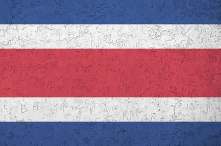 Costa Rica flag depicted in bright paint colors on old relief plastering wall close up. Textured banner on rough background