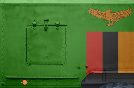 Zambia flag depicted on side part of military armored truck close up. Army forces vehicle conceptual background