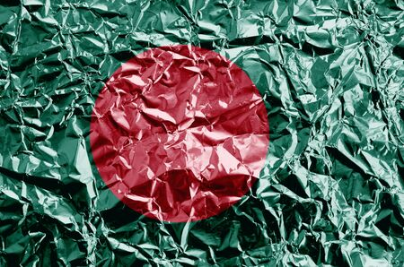 Bangladesh flag depicted in paint colors on shiny crumpled aluminium foil close up. Textured banner on rough background