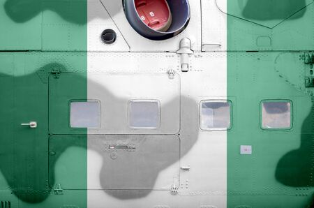 Nigeria flag depicted on side part of military armored helicopter close up. Army forces aircraft conceptual background