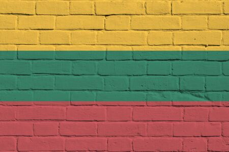 Lithuania flag depicted in paint colors on old brick wall close up. Textured banner on big brick wall masonry background Stock fotó