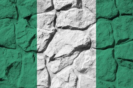 Nigeria flag depicted in paint colors on old stone wall close up. Textured banner on rock wall background