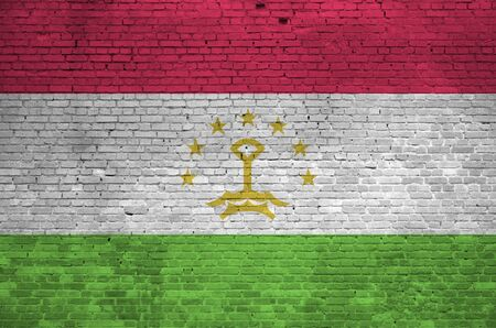 Tajikistan flag depicted in paint colors on old brick wall close up. Textured banner on big brick wall masonry background Stock fotó