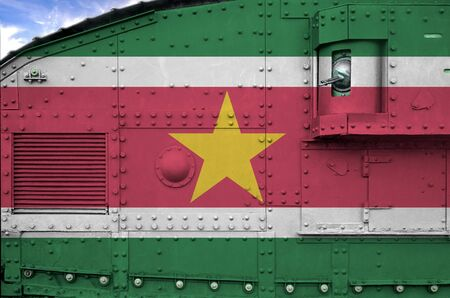 Suriname flag depicted on side part of military armored tank close up. Army forces conceptual background