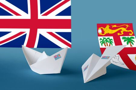 Fiji flag depicted on paper origami airplane and boat. Oriental handmade arts concept