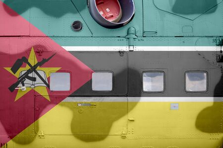 Mozambique flag depicted on side part of military armored helicopter close up. Army forces aircraft conceptual background