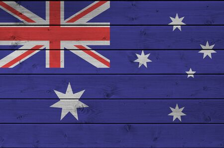 Australia flag depicted in bright paint colors on old wooden wall close up. Textured banner on rough background
