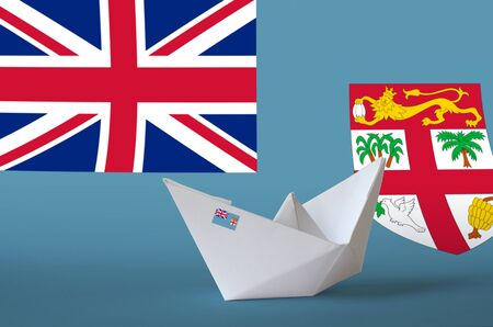 Fiji flag depicted on paper origami ship closeup. Oriental handmade arts concept