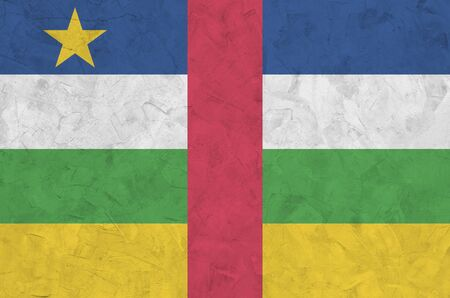Central African Republic flag depicted in bright paint colors on old relief plastering wall close up. Textured banner on rough background